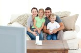 10215491-adorable-family-watching-television-together-sitting-on-the-sofa
